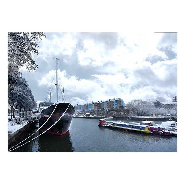 Boat in snowy scene with colourful houses in background