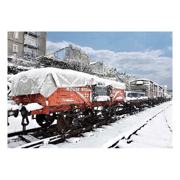 Red train carriage in snow with houses in background